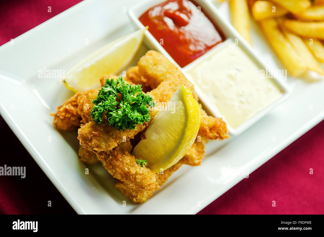 fish fingers and chips on plate classic british food - Stock Image