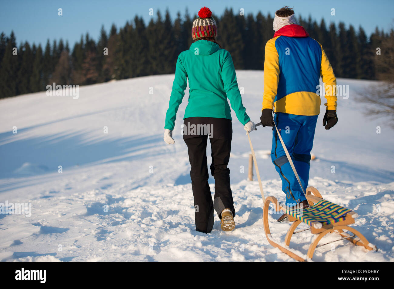 Young sporty couple go sledging on a hill in winter - Stock Image