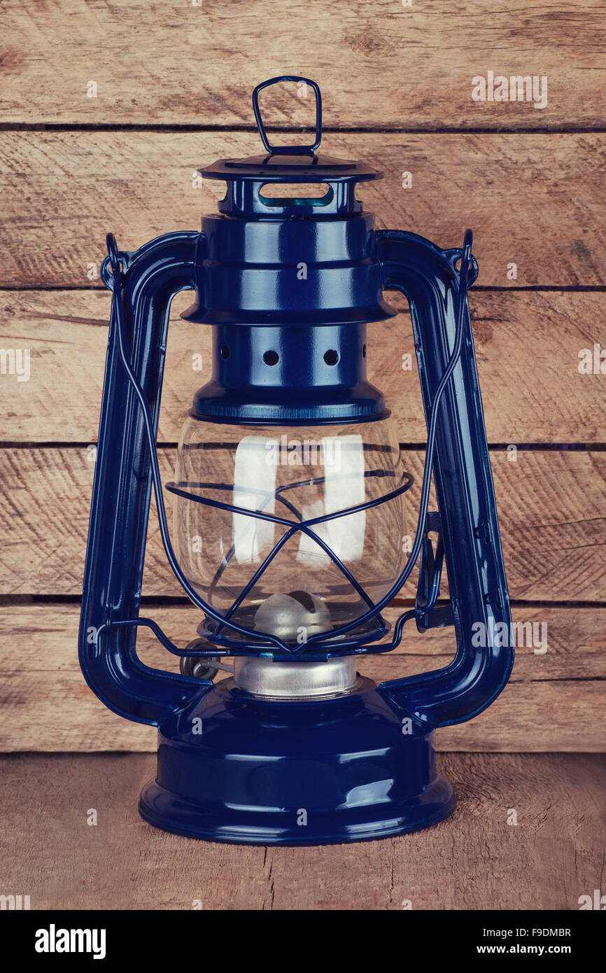 decorative blue kerosene lamp on wooden table Stock Photo