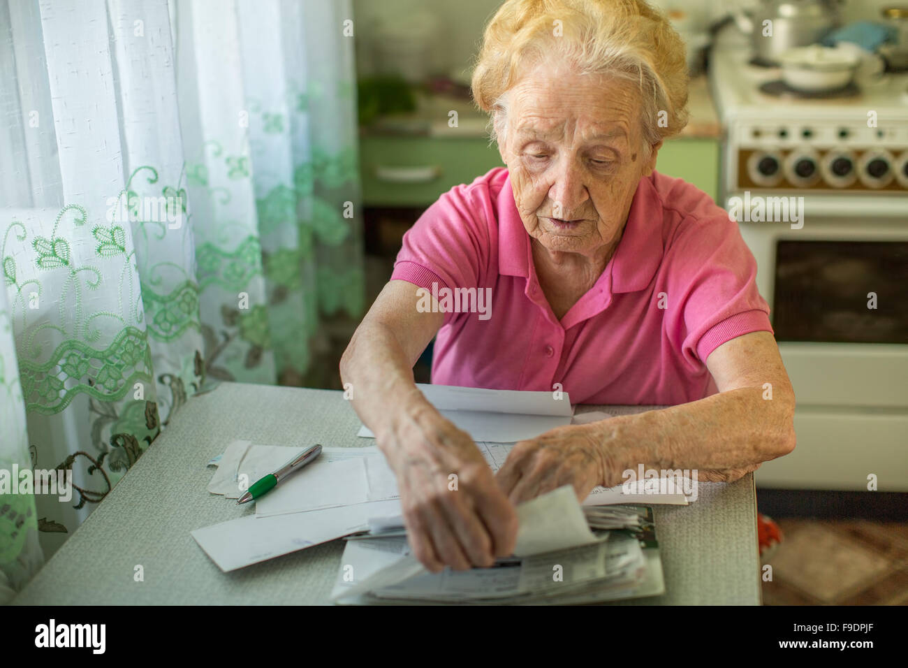 An elderly woman fills in for the payment of utilities. - Stock Image