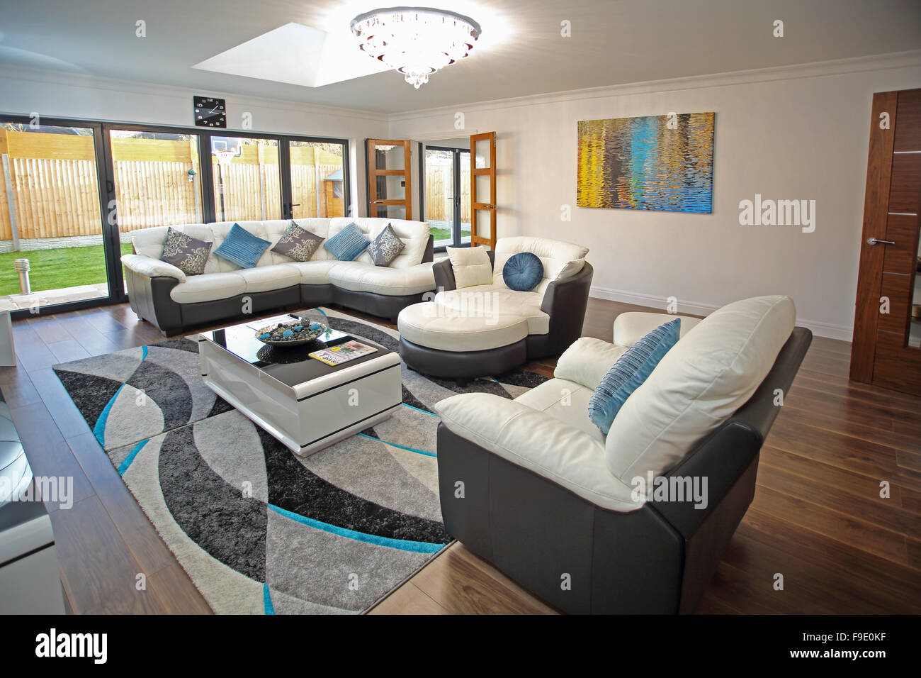 The living room of a newly refurbished house with two-tone leather sofas and bifold doors to the garden - Stock Image
