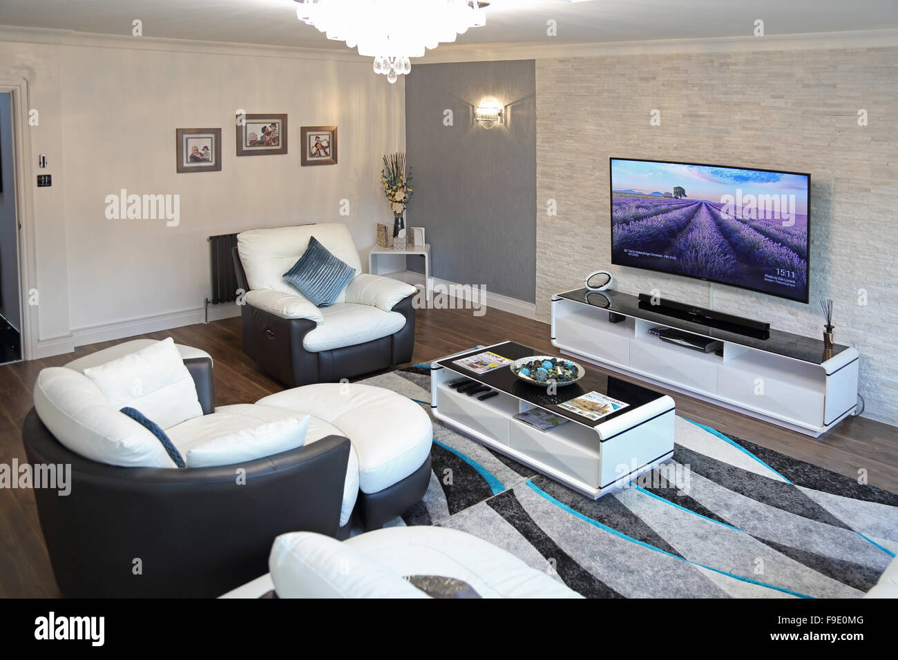 The living room of a newly refurbished house with two-tone leather sofas and large, wall-mounted flat-screen TV - Stock Image
