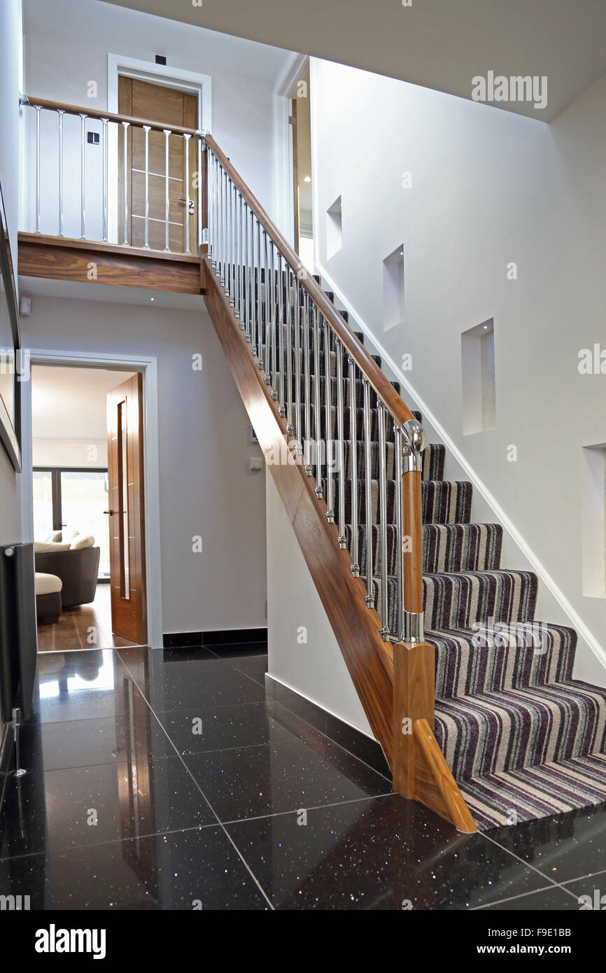 domestic staircase in a newly refurbished London house showing wood and metal banisters, tiled floor and a striped Stock Photo