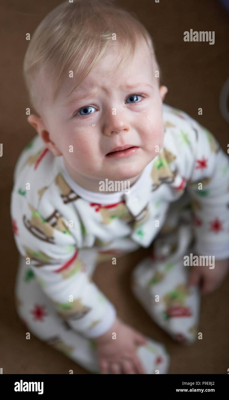 Blonde blond haired sad child crying with tears in his blue eyes - Stock Image