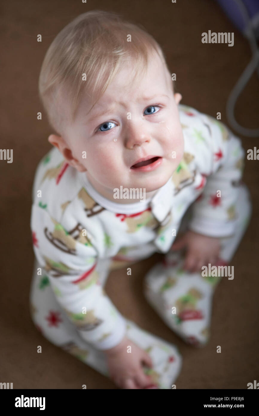 Blonde haired sad child crying with tears in his blue eyes - Stock Image