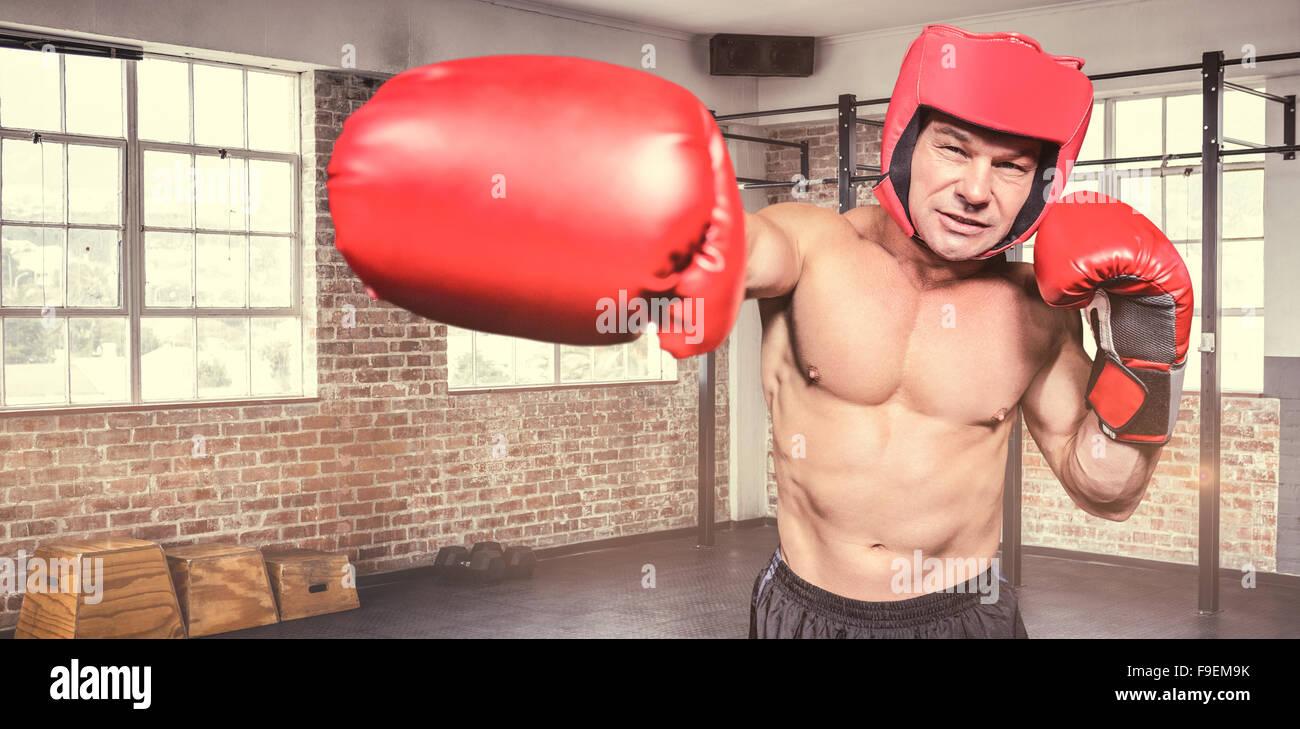 Composite image of boxer punching against black background - Stock Image