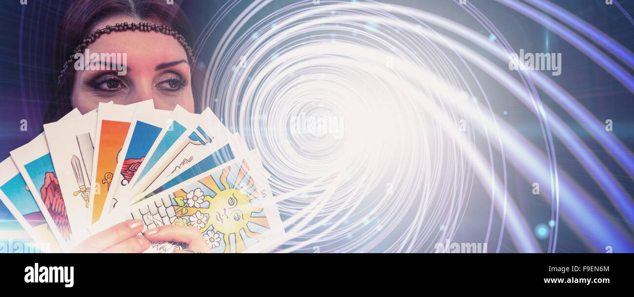 Composite image of fortune teller holding tarot cards while looking away - Stock Image