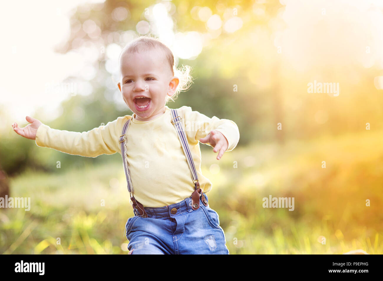 Little boy playing and having fun outside in a park Stock Photo