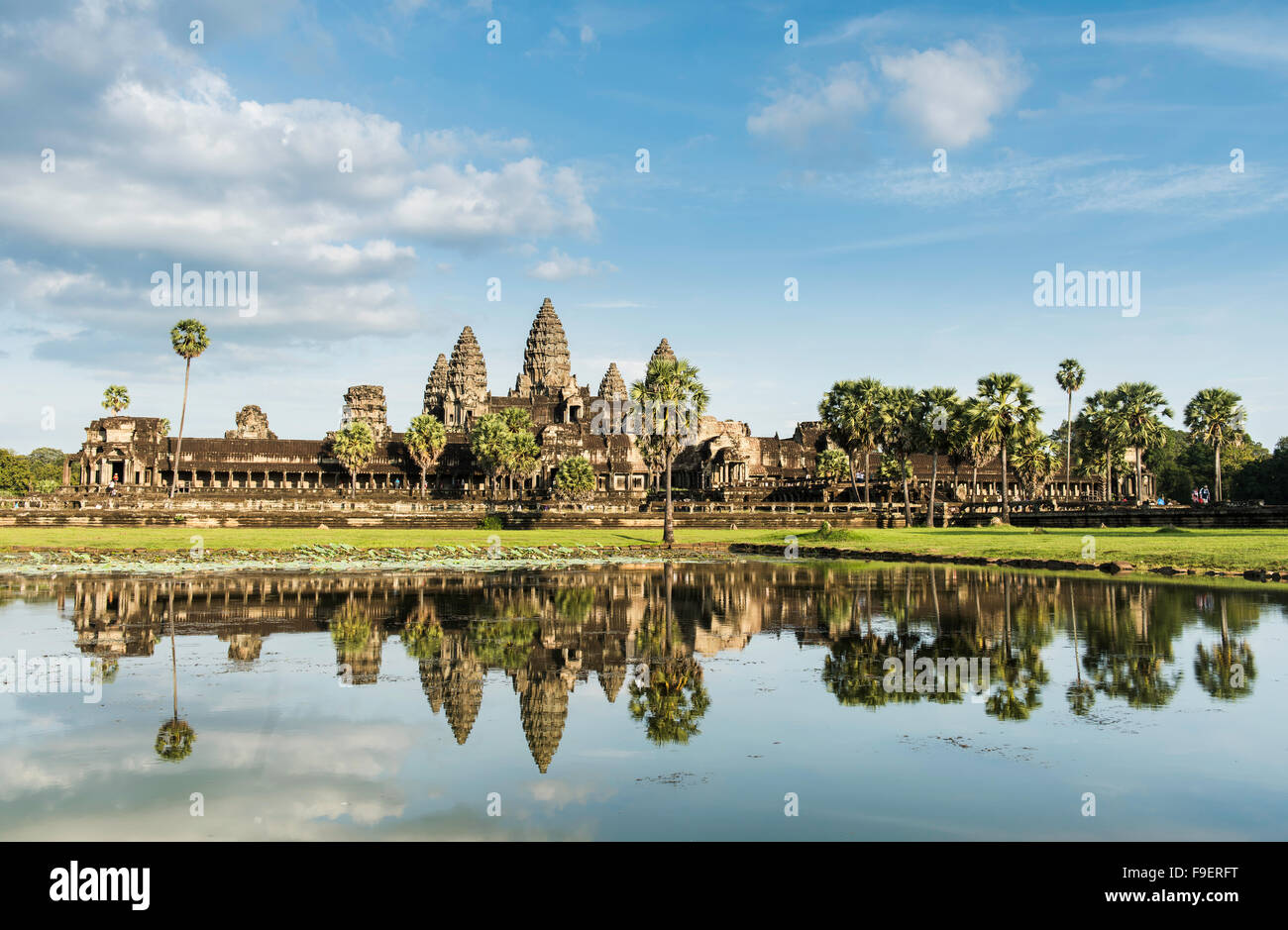 Angkor Wat temple reflected in a foreground pool after monsoon rains. - Stock Image