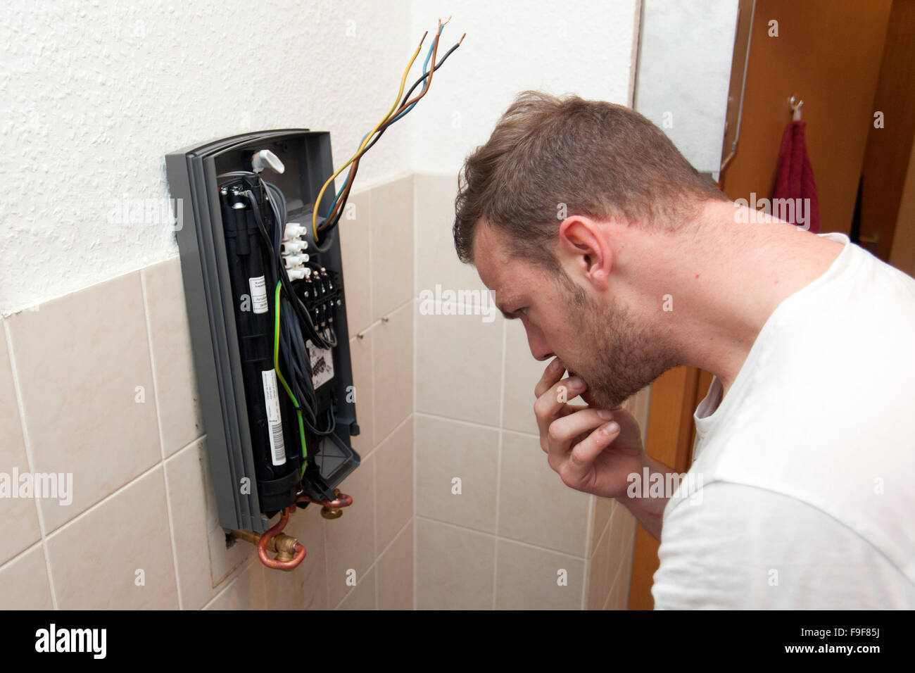 Plumber Attaches A Continuous Flow Water Heater In The Bathroom Wiring Circuit
