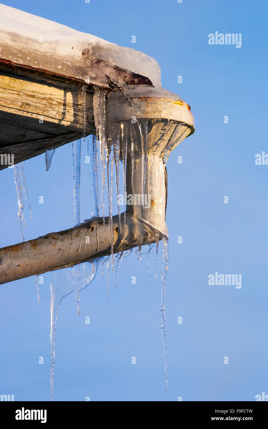 Icicles ice on corner of roof at the mouth drainpipe - Stock Image