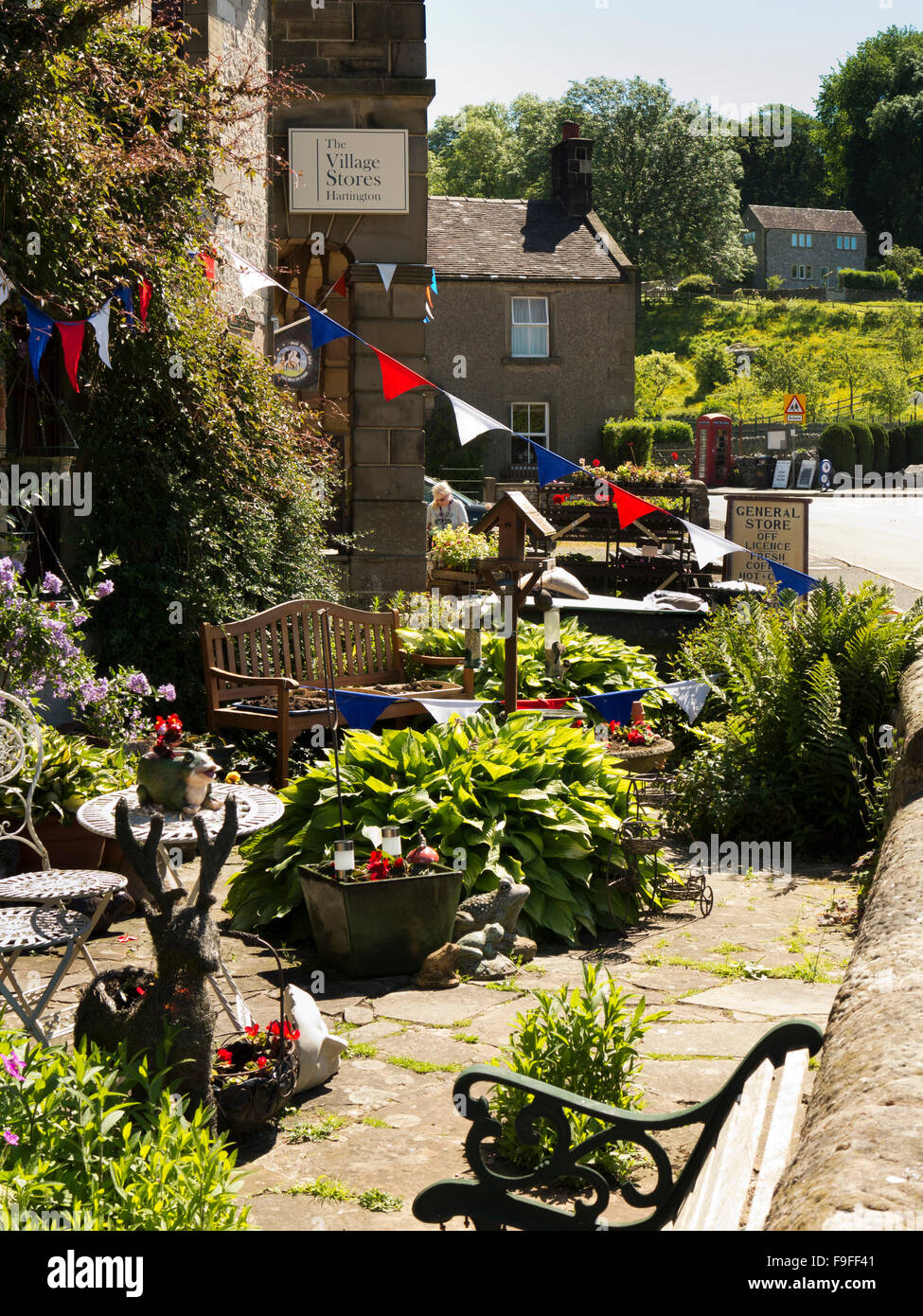 UK, England, Derbyshire, Hartington, Village Stores, bunting above outdoor café tables - Stock Image