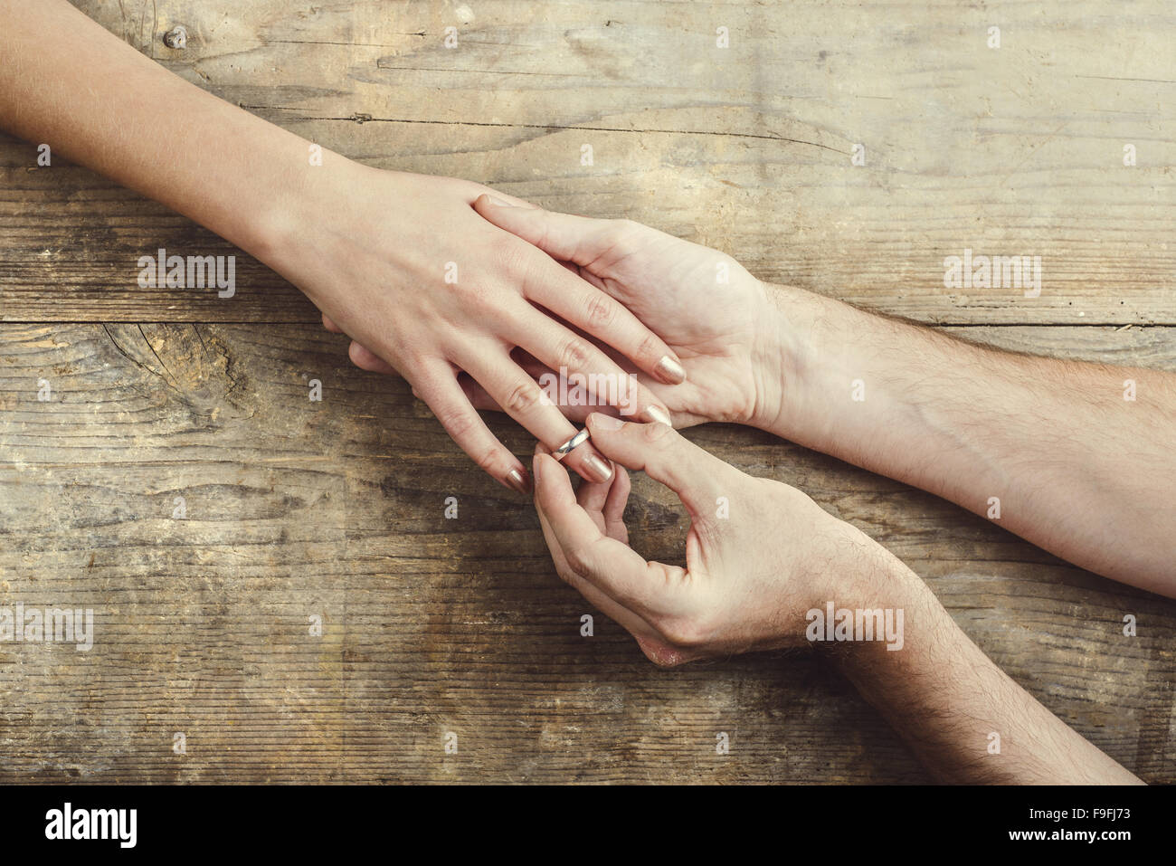 Man putting on engagement ring tenderly to his woman. Studio shot on a wooden background, view from above. - Stock Image
