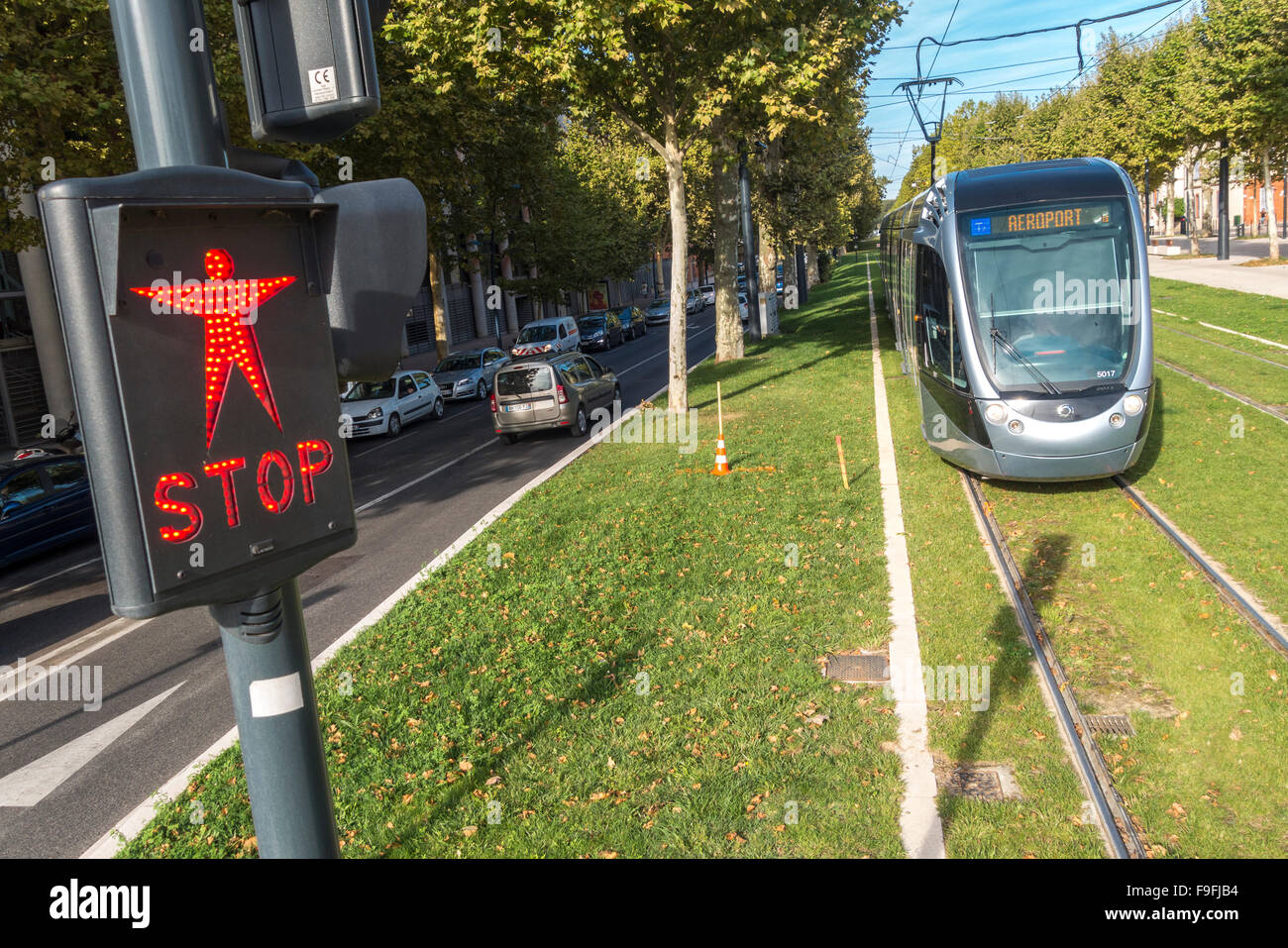 Toulouse France Tramline 1 to Toulouse-Blagnac Airport waiting at a pedestrian crossing in front of the Palais de - Stock Image