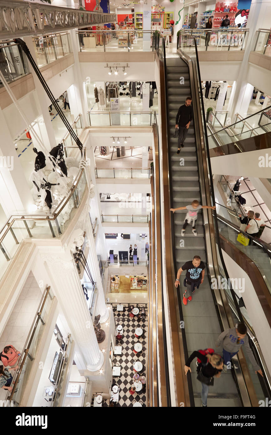 Selfridges department store interior, escalators with customers and visitors in London - Stock Image