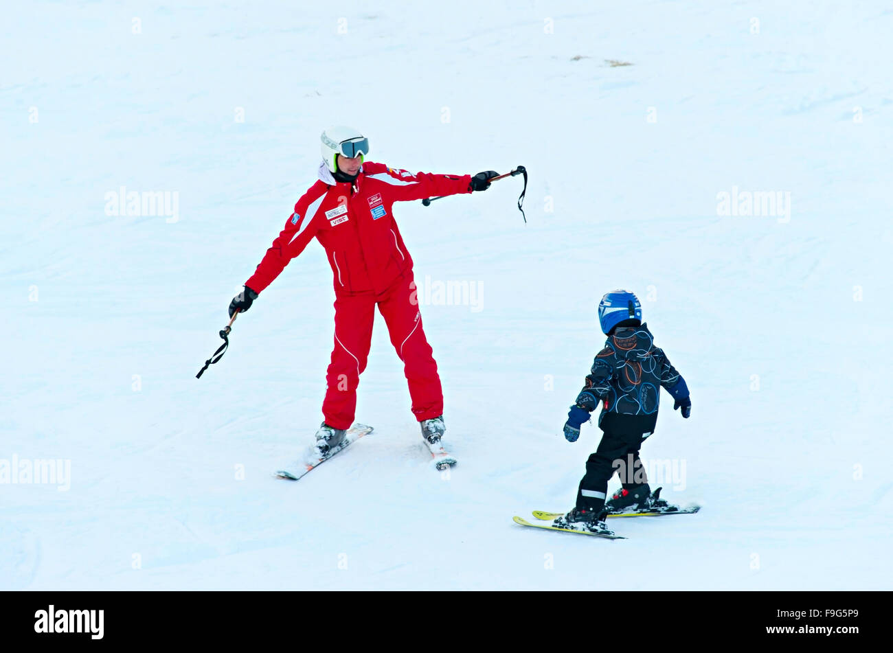 Instructor give a first ski lesson for small skier in Bukovel. - Stock Image