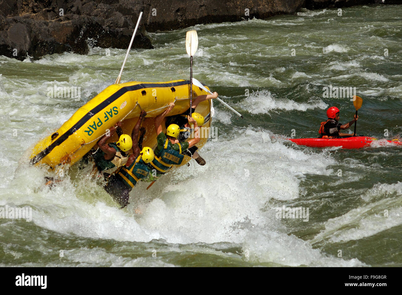 Yellow raft flipping on a wave at The Boiling Pot on the Zambezi River in Zambia Stock Photo