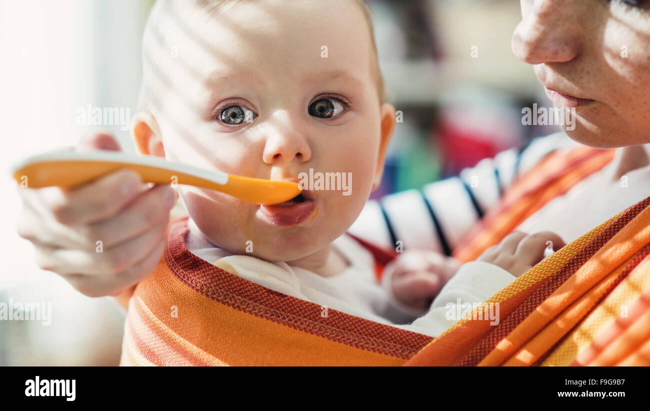 Young mother feeding her little daughter that she has in a baby carrier - Stock Image