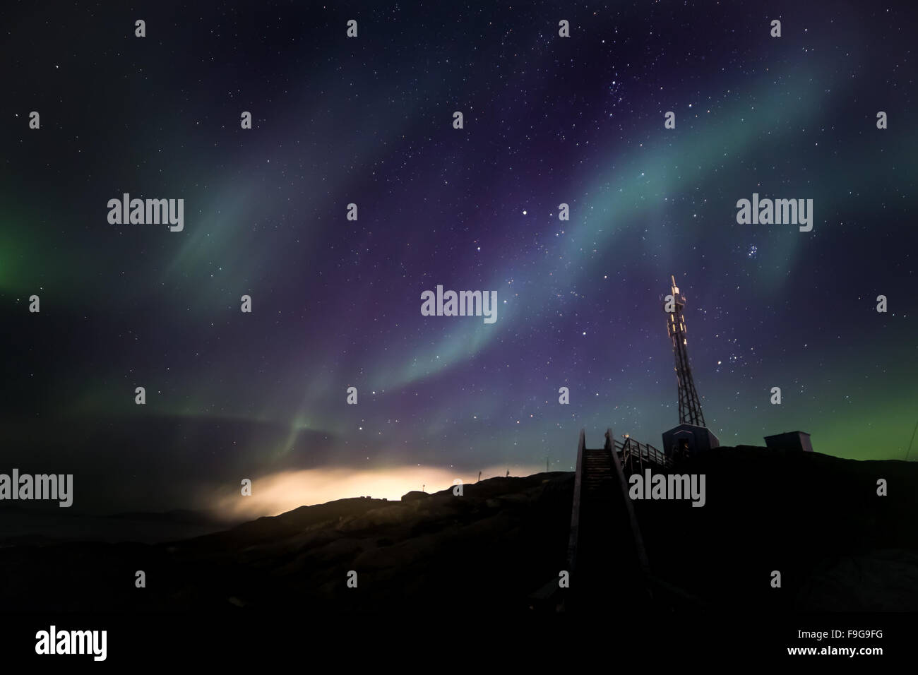 Green extensive Northern lights shining over the starlight sky and