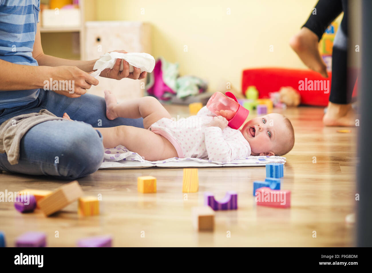 Young hipster father changing nappy to his little baby daughter - Stock Image