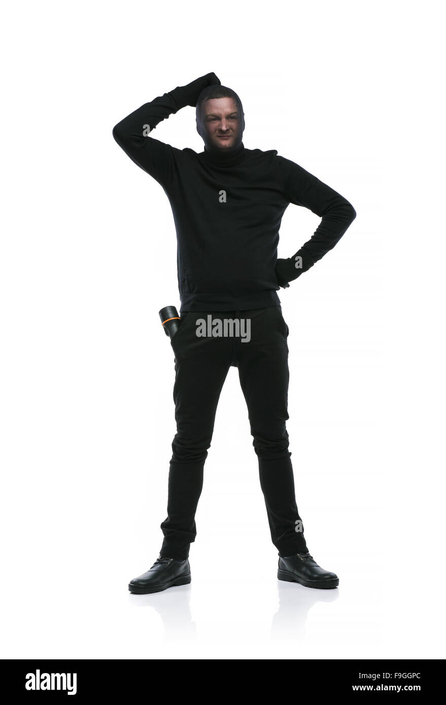 Thief in action with balaclava on his face, dressed in black. Studio shot on white background. - Stock Image
