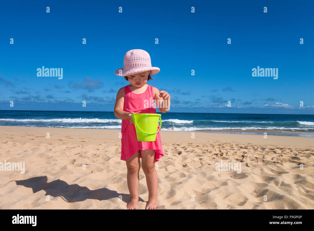 Toddler girl holding a green bucket at the beach, Kauai island - Stock Image