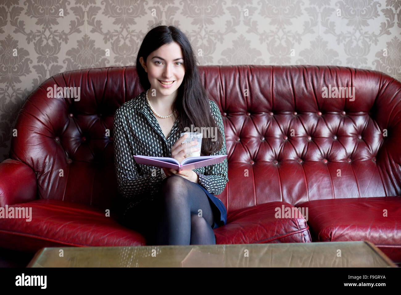 Young woman sitting on a sofa with a book and a drink - Stock Image