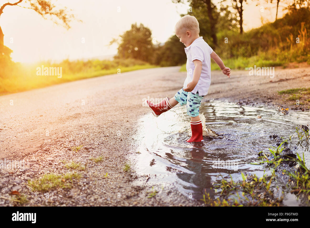 Little boy playing outside in a puddle Stock Photo