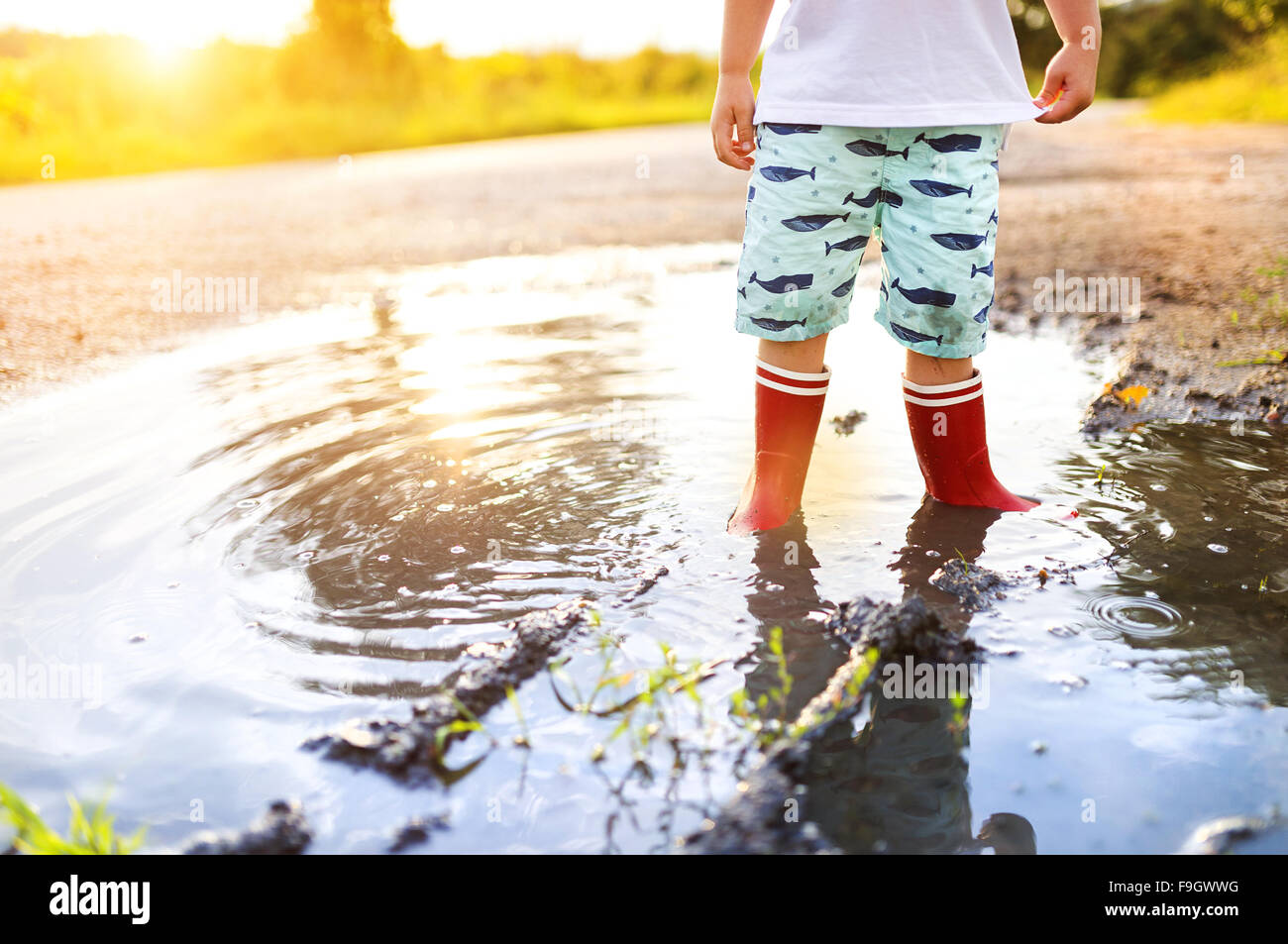 Little boy playing outside in a puddle - Stock Image