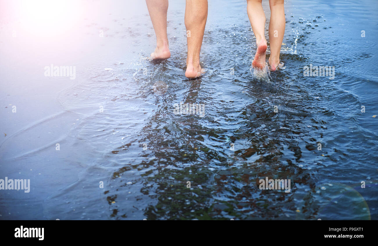 Unrecognizable woman and man walking barefoot through a puddle - Stock Image