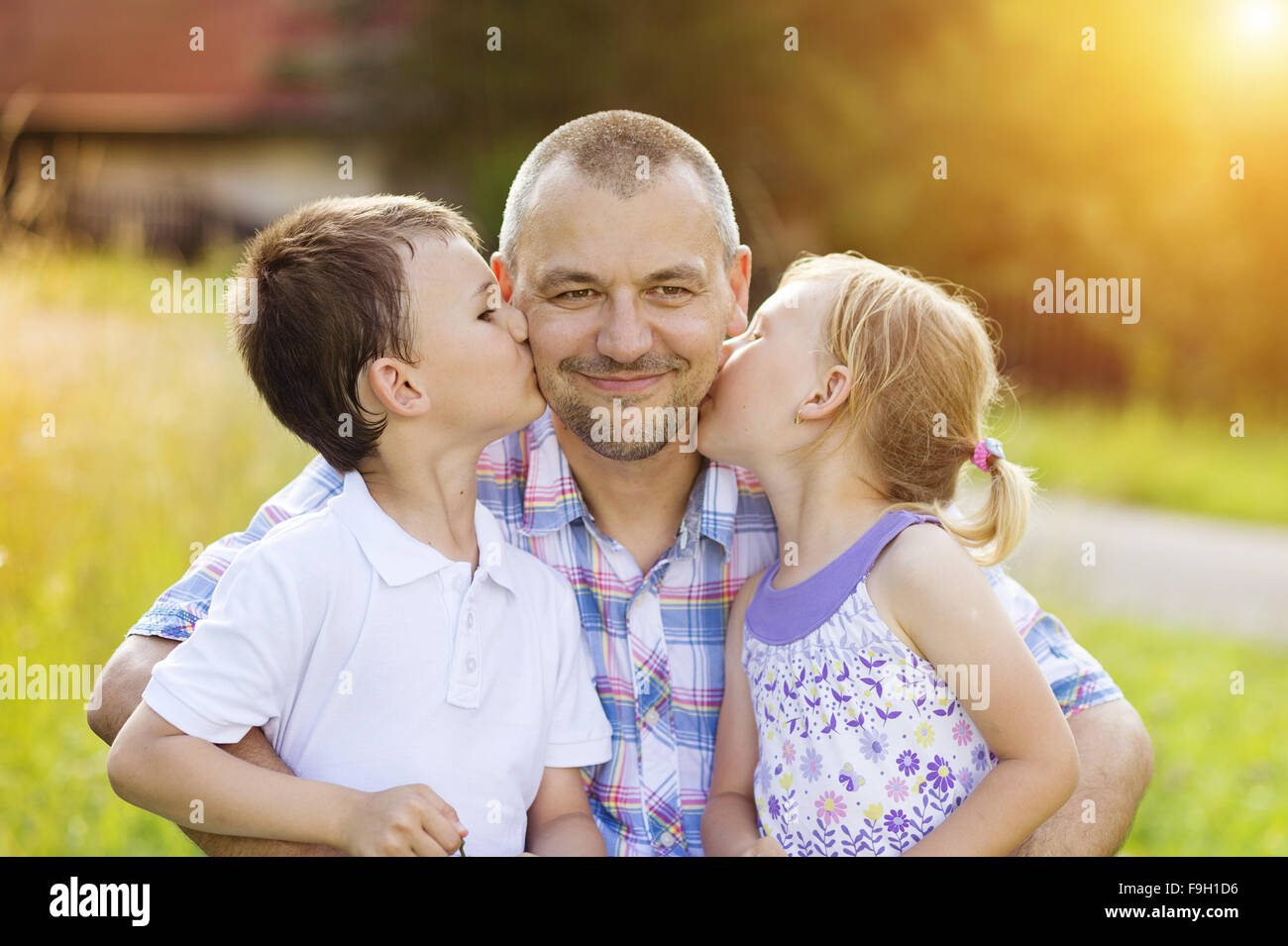Father with his two children spending time together outside in green nature. - Stock Image