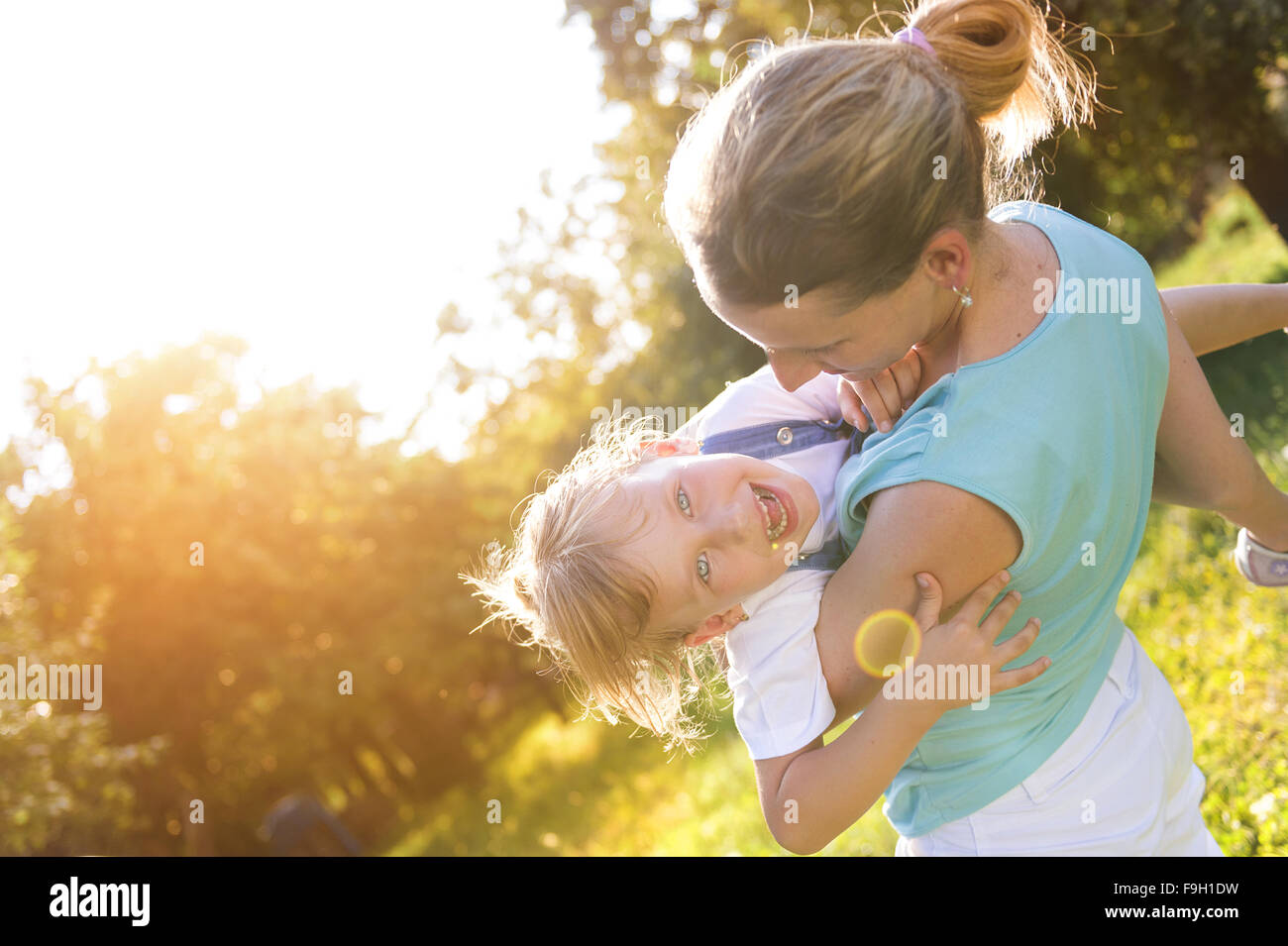Happy little girl having fun with her mother in green nature. Stock Photo