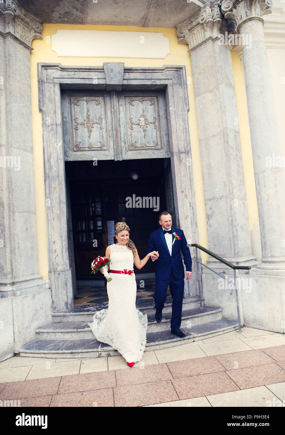 Bride and groom walking out of the church holding hands - Stock Image