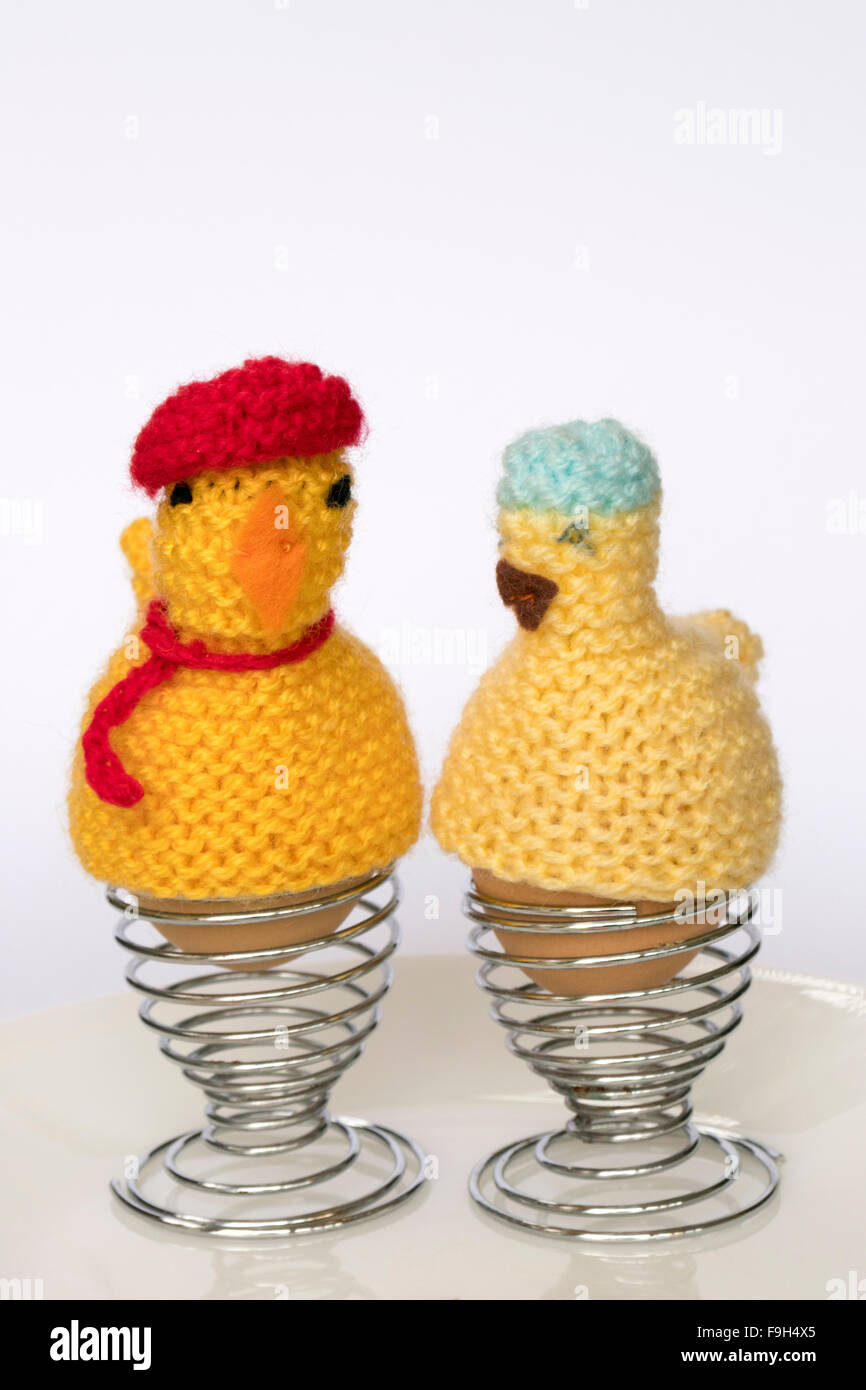 Two boiled eggs in egg cups with knitted funny  chicken egg cosies on them - Stock Image
