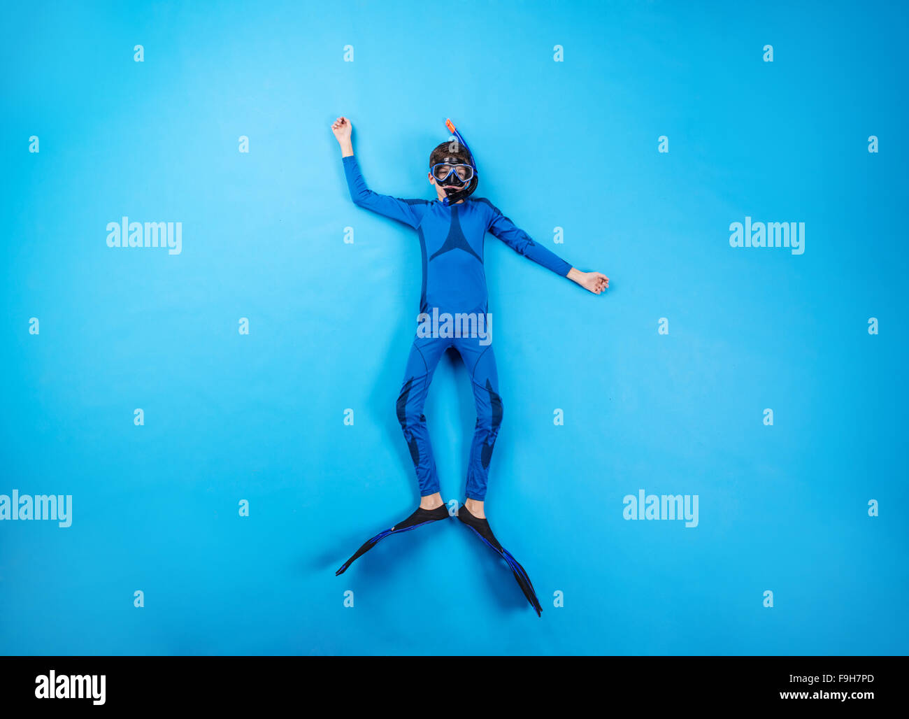 Children scuba diving deep in the sea. Studio shot on a blue background. - Stock Image
