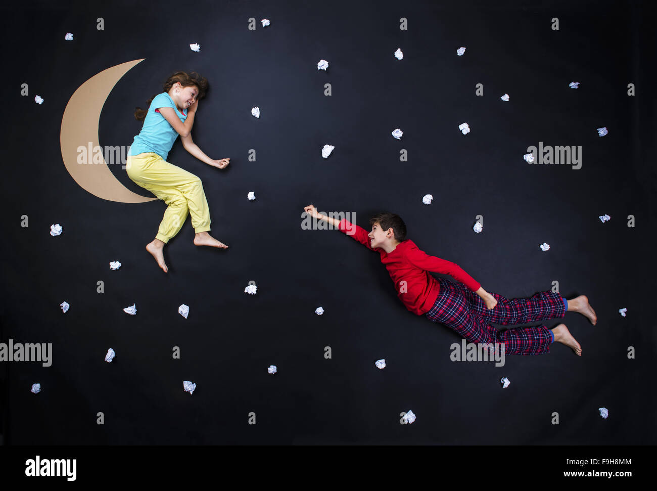 Children getting ready for bedtime. Studio shot on a black background. - Stock Image