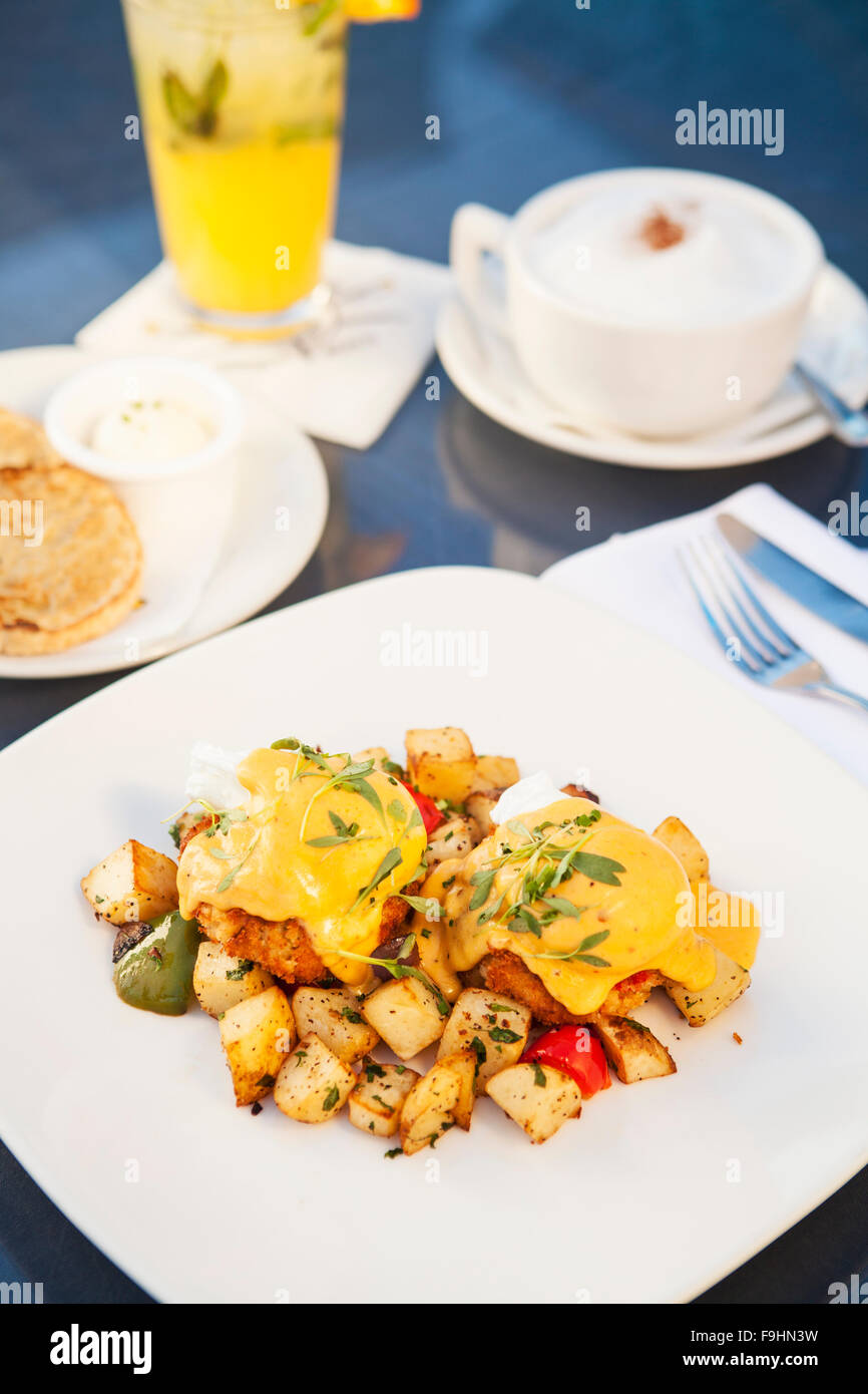 poached eggs and Dungeness crab cakes on breakfast potatoes, chipotle hollandaise, avocado and pico de gallo Stock Photo