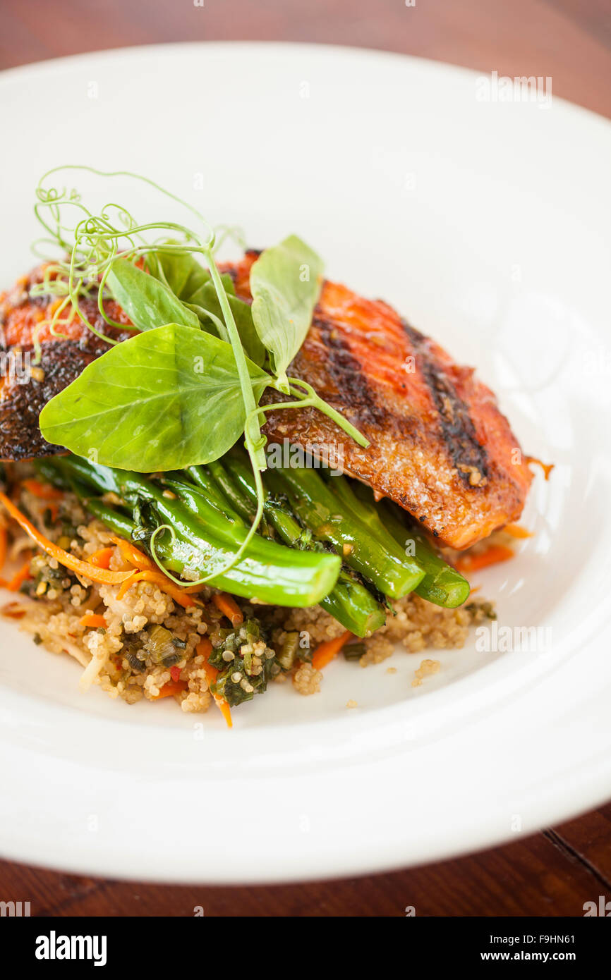grilled Alaskan salmon with sweet and spicy broccolini, tomato miso quinoa and daikon-carrot kimchi, Ocean Grill, - Stock Image