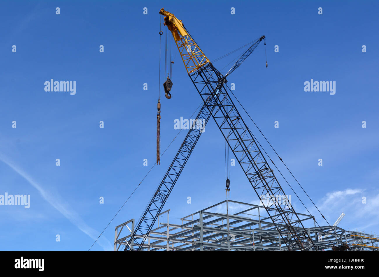 Cranes in construction site against blue sky. Construction work concept - Stock Image