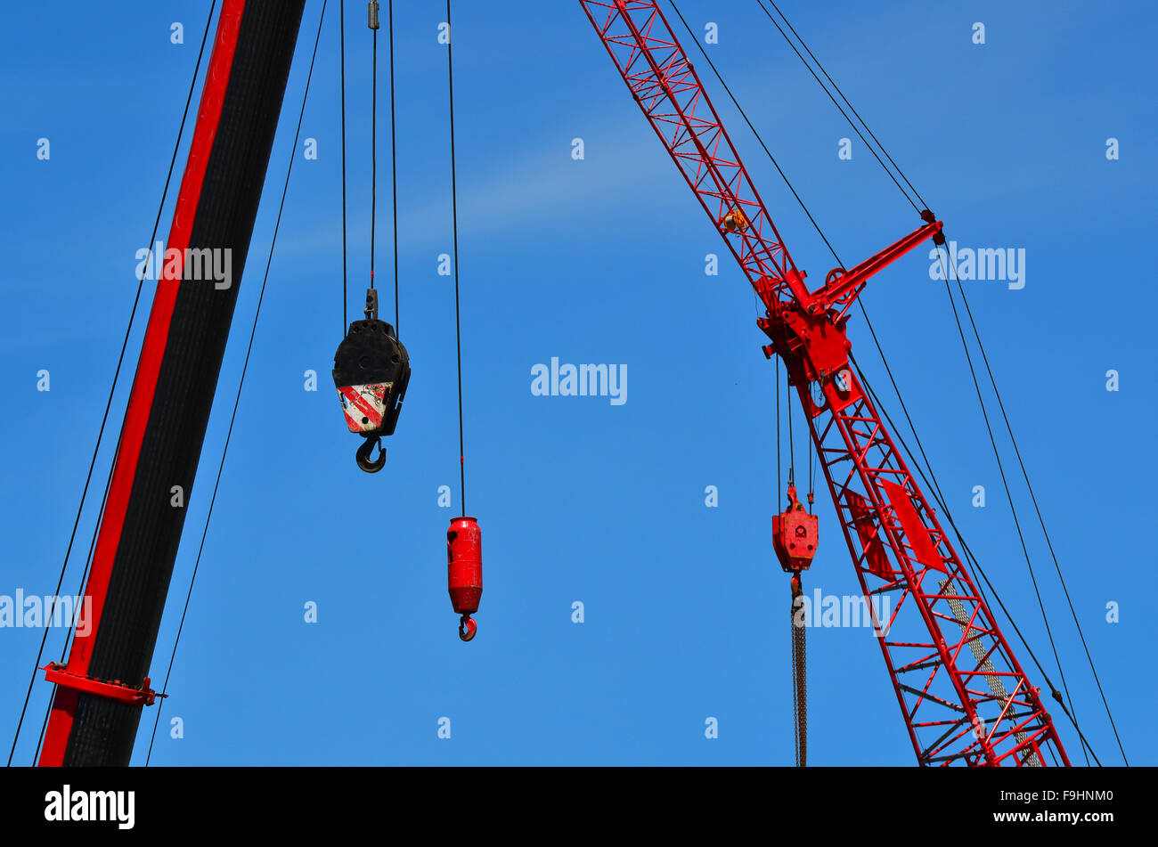 Red cranes in construction site against blue sky. Construction work concept - Stock Image