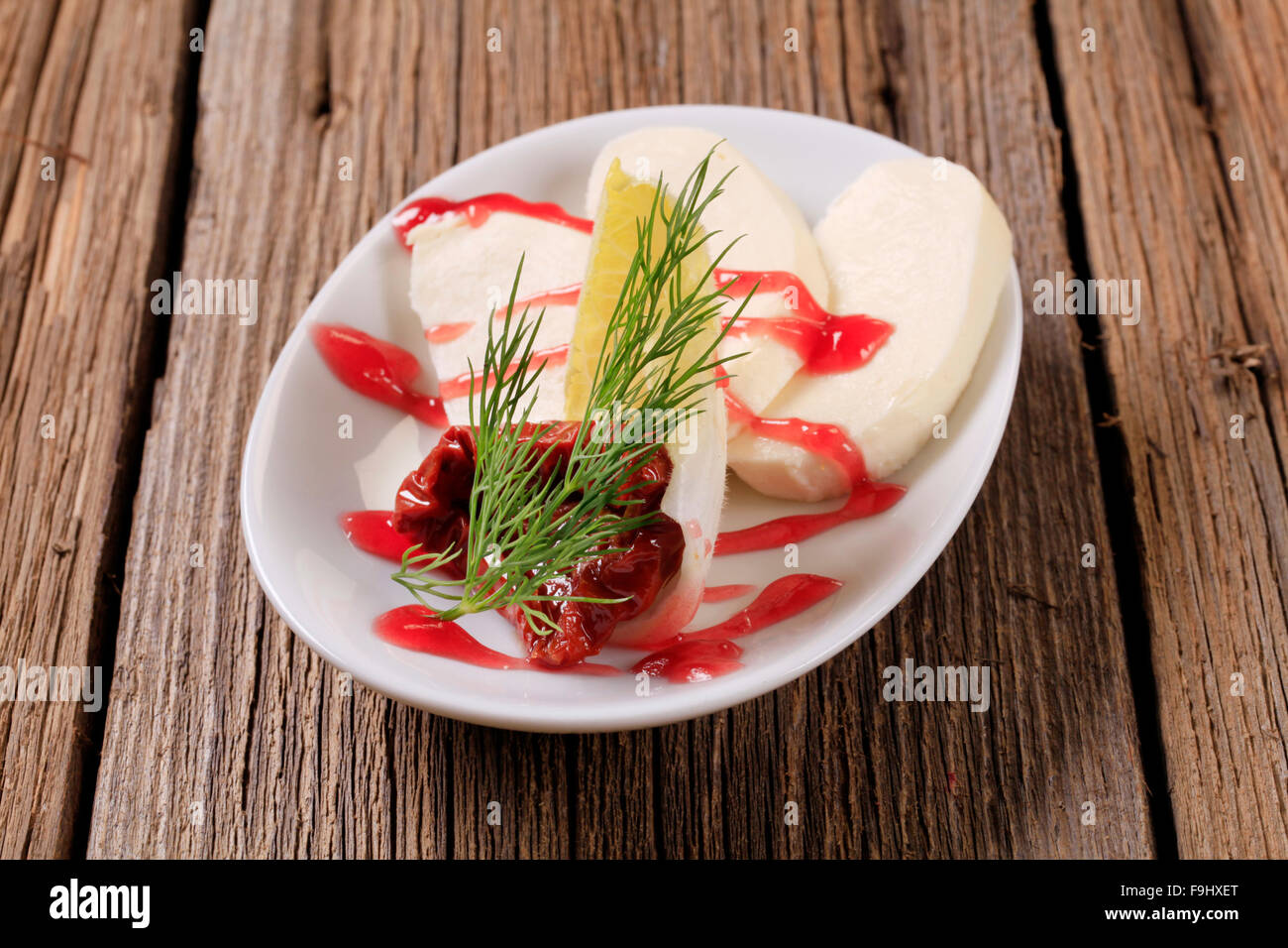 Mozzarella cheese with garnish and raspberry balsamic reduction Stock Photo