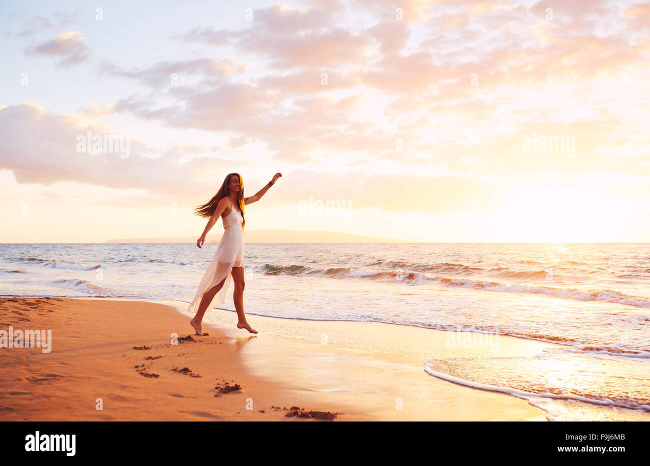 Happy carefree woman dancing at sunset on the beach. Happy free lifestyle concept. - Stock Image