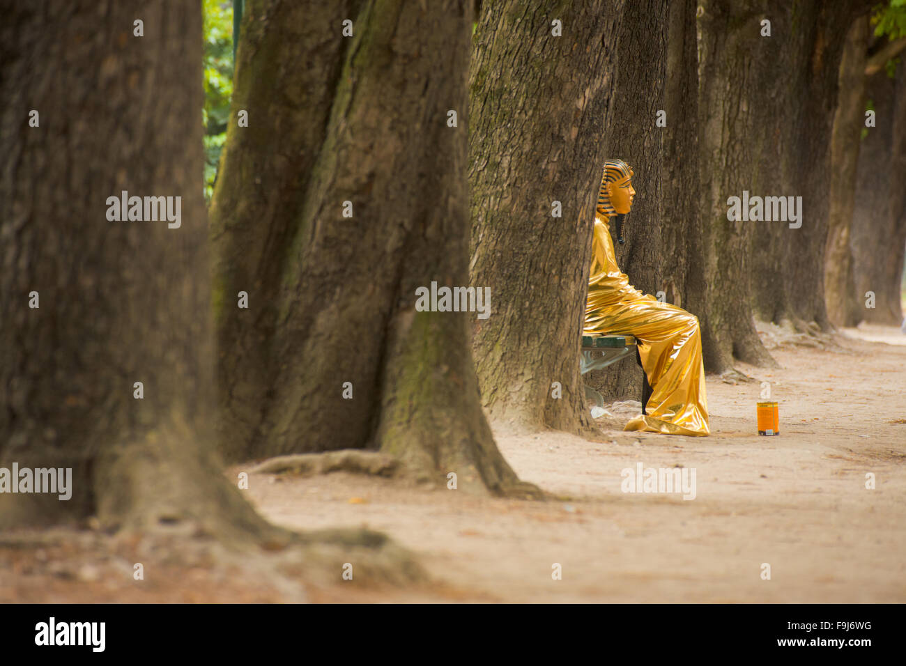 Street performer in Egyptian pharaoh costume sits lazily on the tree-lined sidewalk of the Champs d'Elysees - Stock Image