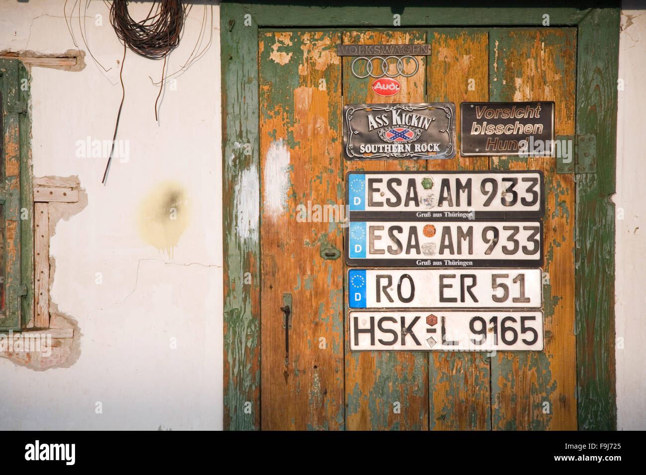 Old workshop doors with few German car licence plates. Concept. Travel, cars, service, garage, repair shop, workshop. - Stock Image