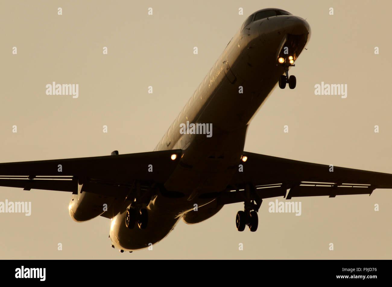 A Silhouette of a Lufthansa Regional Canadair CRJ 701 Landing in Leipzig - Stock Image