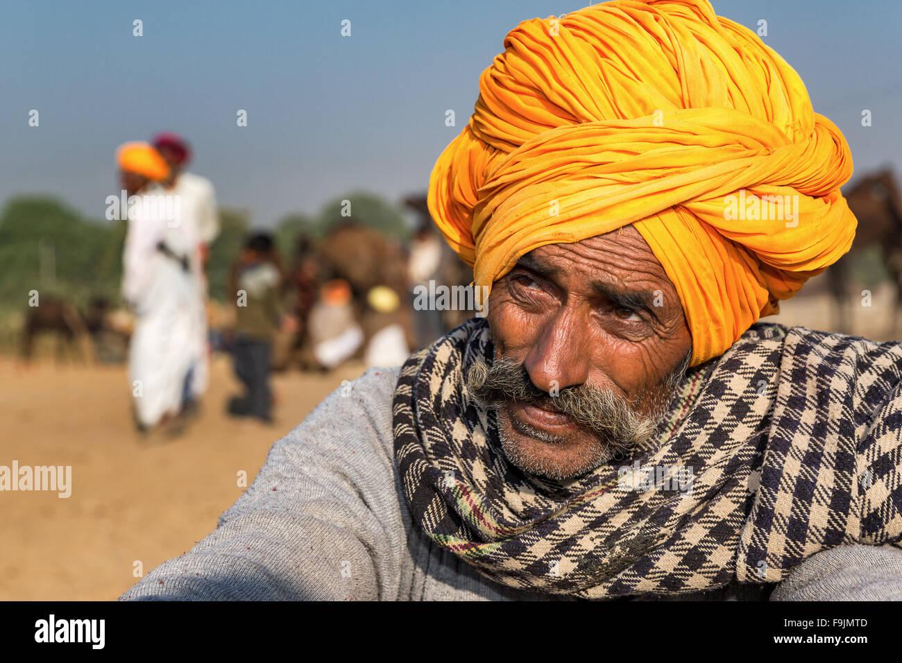 Portrait of a senior Rajasthani with a yellow turban, Pushkar Camel Fair, Rajasthan, India - Stock Image