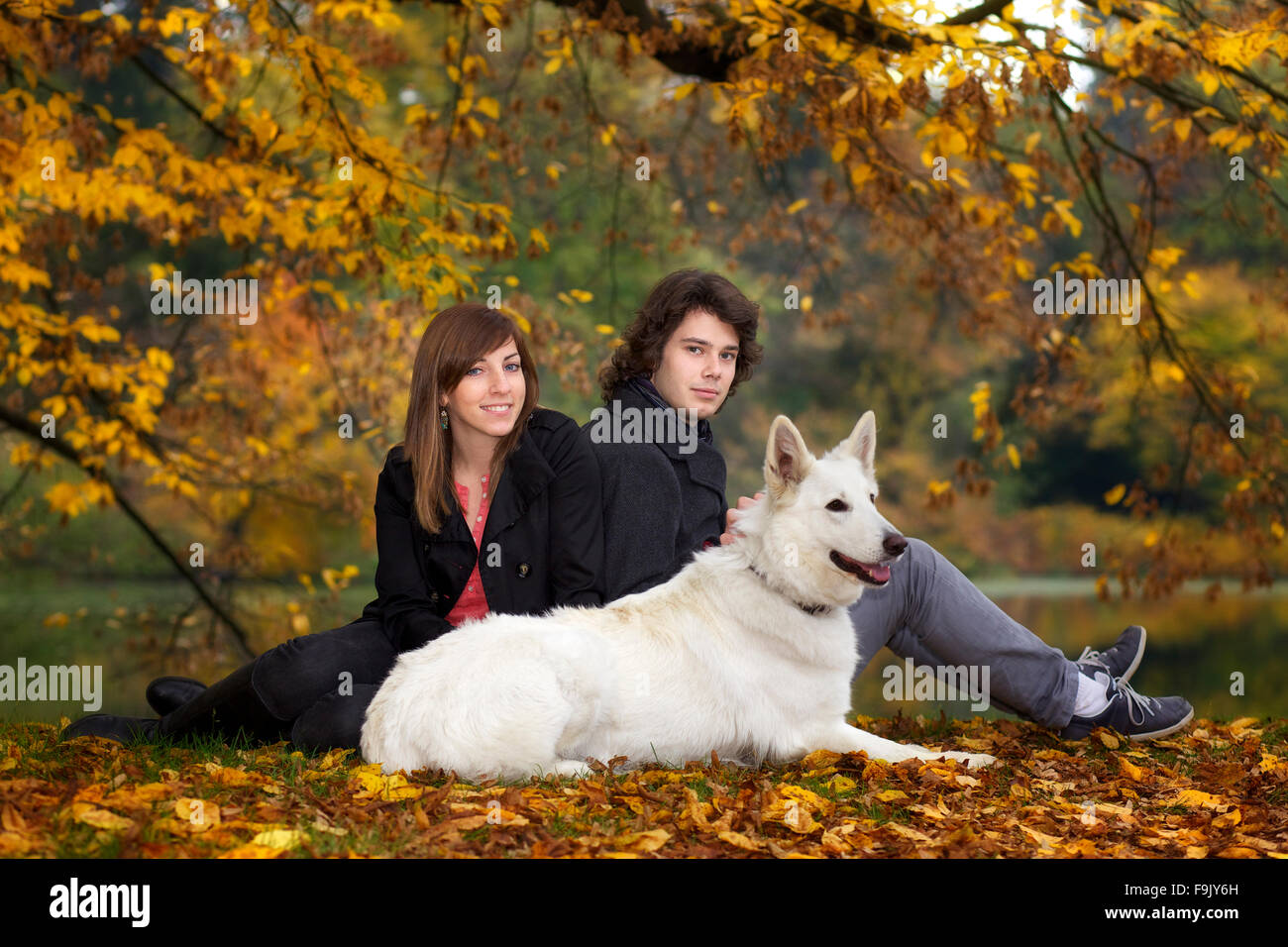Young couple sitting in a park - Stock Image
