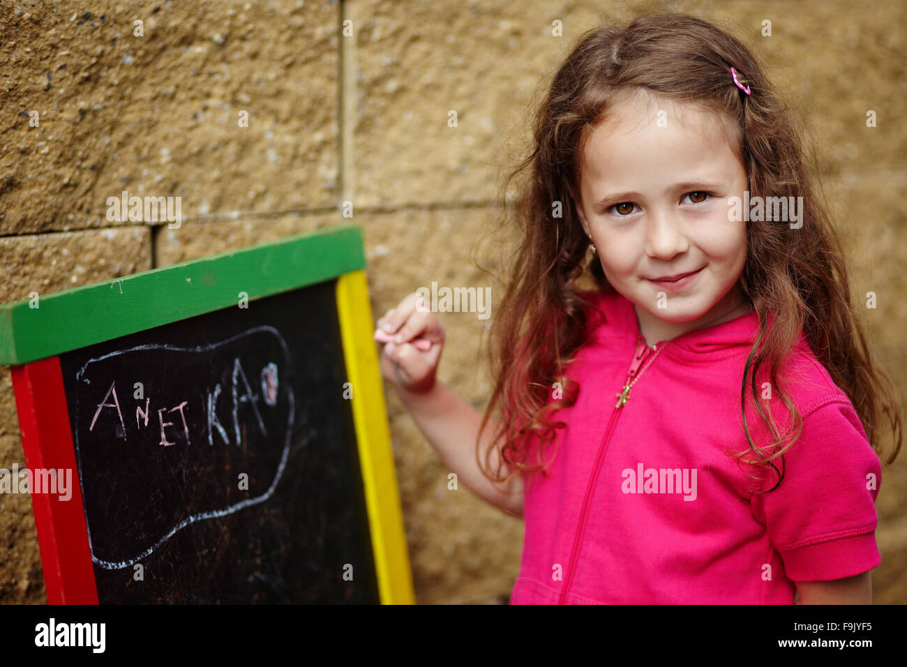 A girl writting on a board - Stock Image