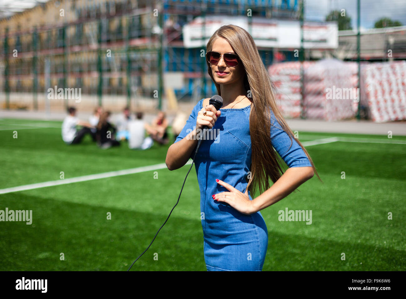 Pretty girl-reporter with microphone on a stadium. - Stock Image