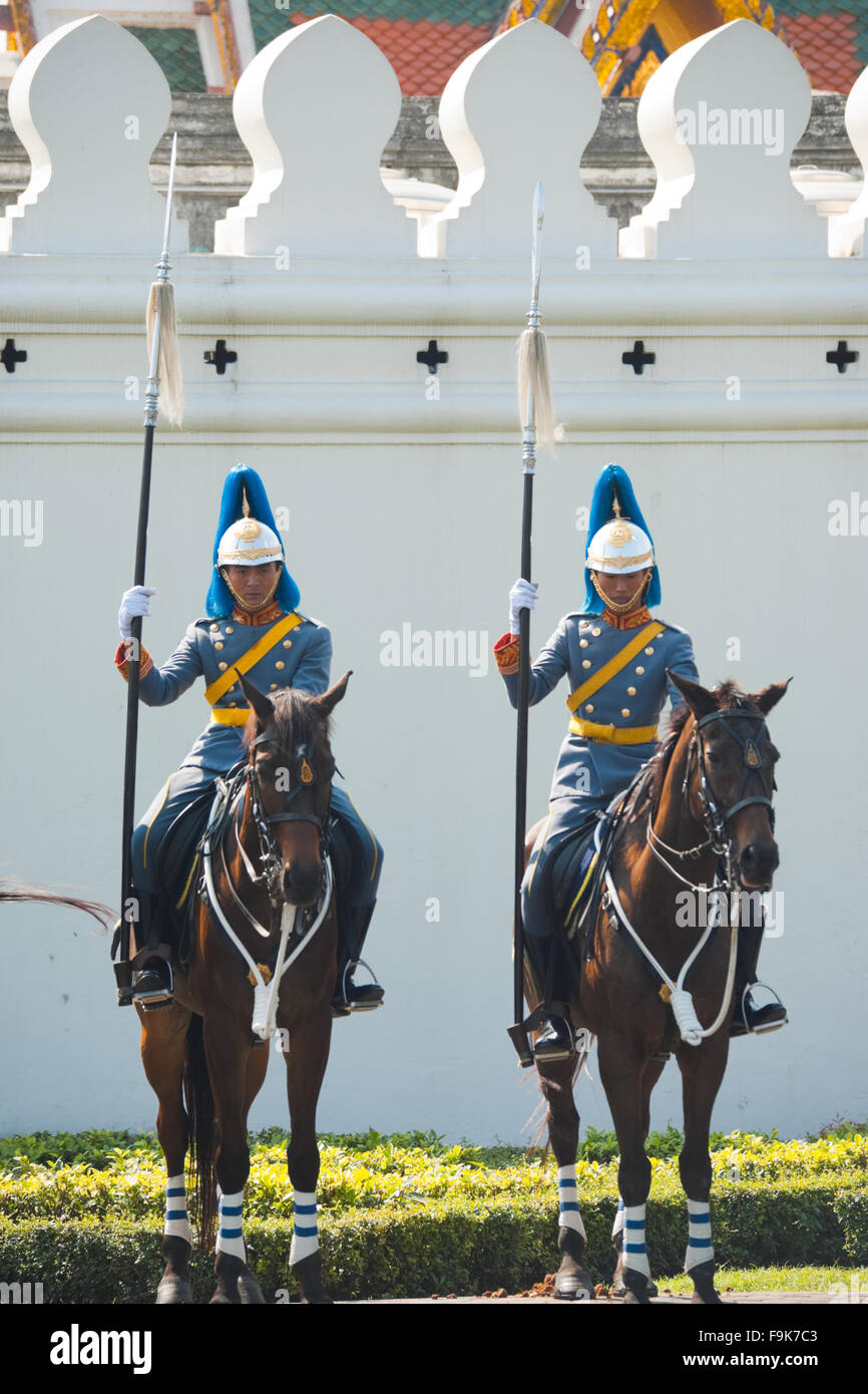 Two members of an elite squad, the Thai Royal Mounted Guard on horseback stand in formation at white wall of the Stock Photo